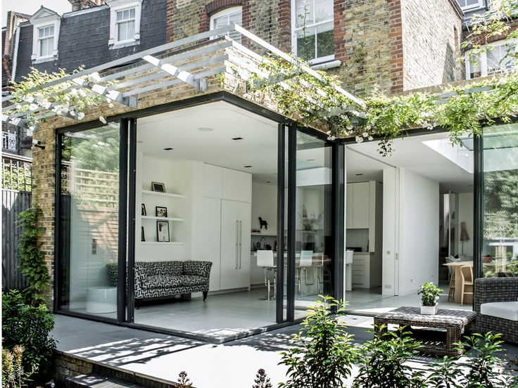 Kitchen extension design with glass sliding doors creates light filled family kitchen glass box. Charles Barclay Architects