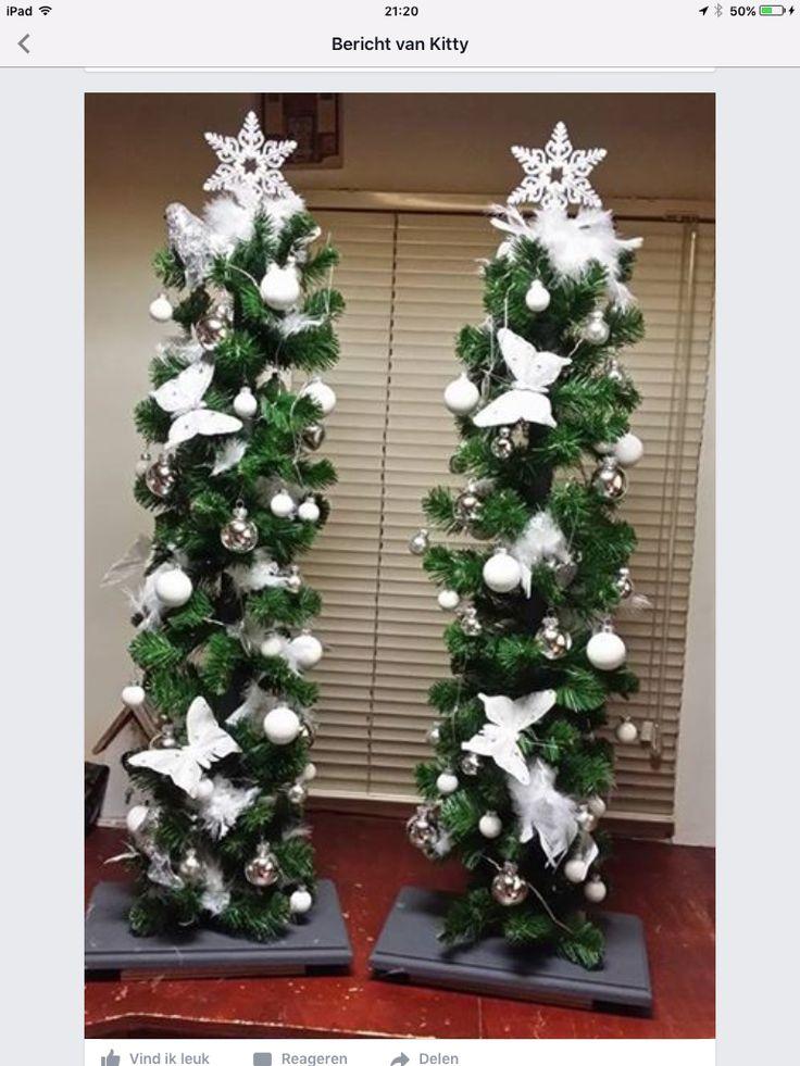 Bezemstelen op plankjes, versieren met nepguilande op echte takken met ty rips en daarna lichtjes en kerstversiering , bij de voordeur