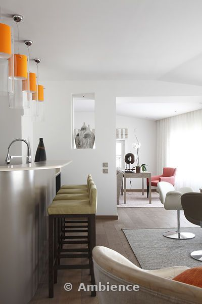 Orange Pendant Lights And Barstools Lining Up Along Kitchen Counter With View Through Opening To Study