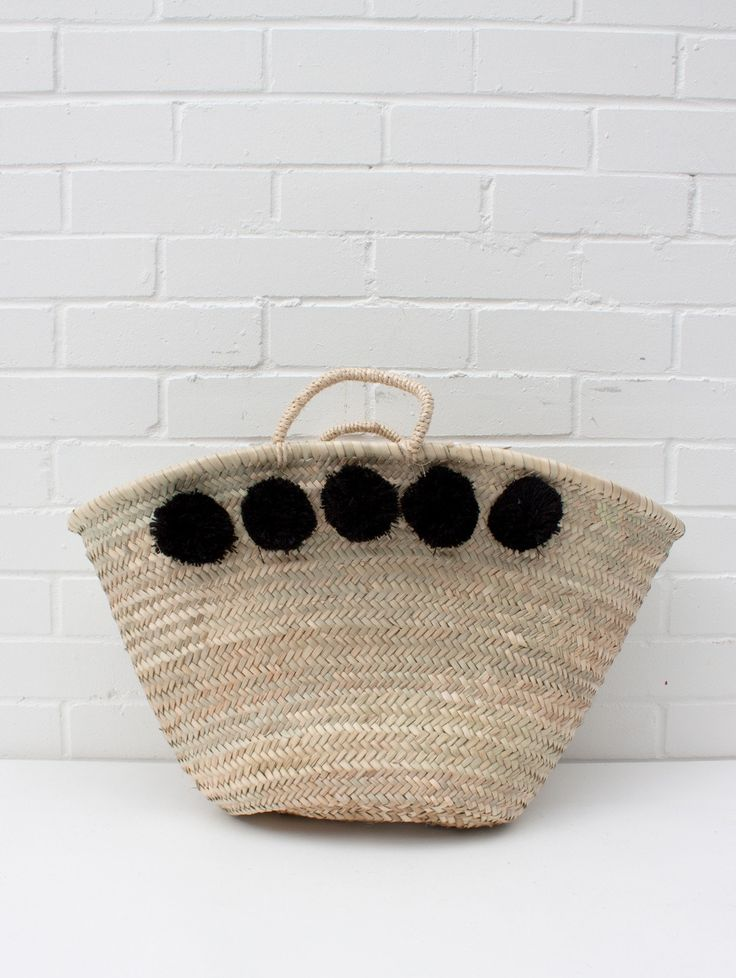 pom pom basket by violet and percy shop The Market Pom Pom Baskets from Bohemia, a French market style basket handwoven from palm leaf with a natural sisal cord handle and 5 black fluffy pom poms on each side. A pretty and practical shopping basket, statement beach bag, and storage basket for the around the home, it could even become a colourful laundry basket.Ethically Handmade in MoroccoSize/ L55 x H35 cmPalm Leaf, Sisal & Wool Pom Poms
