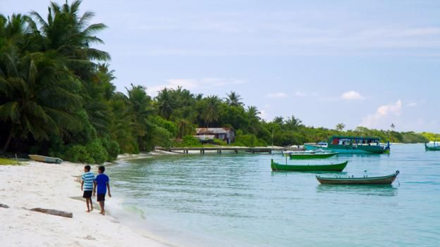 The Maldives you can actually afford... stay for a week in a village guesthouse for the cost of 1 night at a luxury resort. | Walking along a village beach (Credit: Credit: Diane Selkirk)