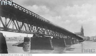 Opis obrazu: Most drogowy we Włocławku - widok ogólny. Widoczny fragment bazyliki katedralnej Najświętszej Maryi Panny  Autor: Arentowicz, Włocławek