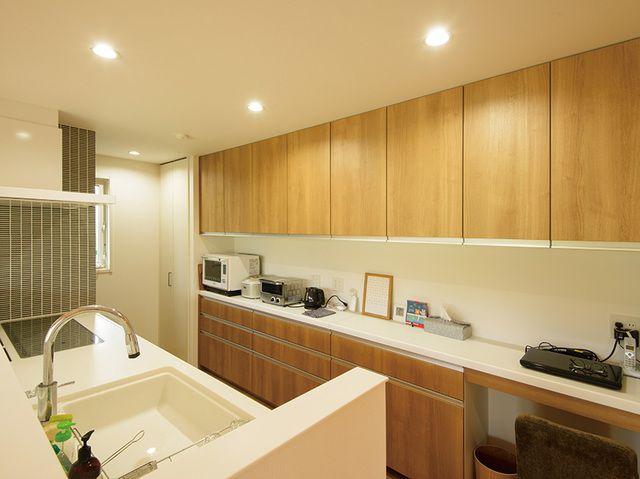 壁一面が収納になっている機能的なキッチン。壁にあしらわれたタイルが可愛らしい。