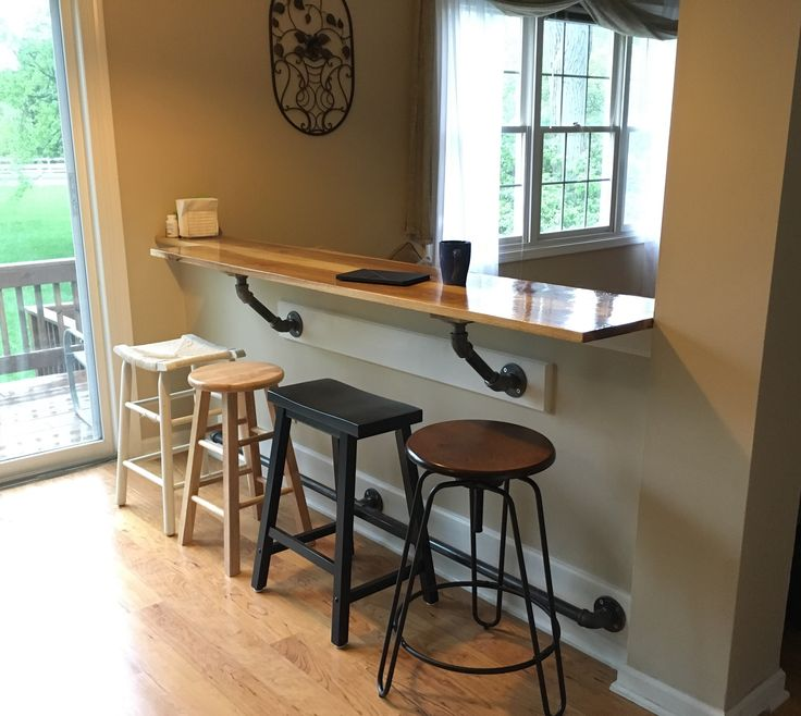 My bar on the half wall. Hickory Bar Top with galvanized pipe supports and foot rail. Mismatched stools.