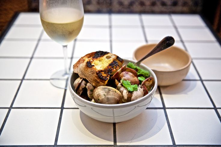 Manila clams steamed open in vinho verde with cilantro and chopped spring garlic are simple and wonderful, especially when you soak some grilled bread in the pan sauce. (Photo: Benjamin Norman for The New York Times)