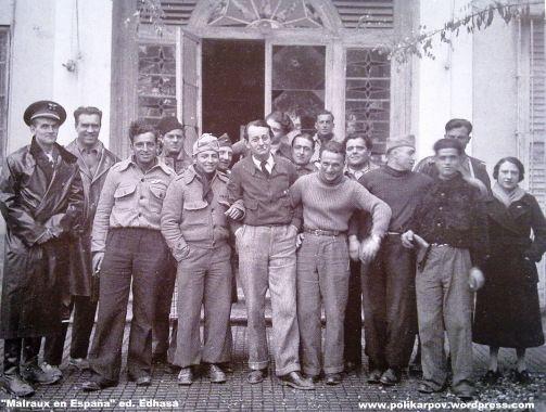 """Spain - 1936. - GC - André Malraux al medio, con las manos en los bolsillos, con un """"pitillo"""" en la boca, y cogido por algunos de sus miembros. Es una de las fotos más populares de este personaje, que fue tomada en Torrent, en lo que parece ser la puerta trasera del Hort de Trènor. A la izquierda del todo, con abrigo de cuero y gorra de plato reglamentaria, se encuentra Paul Nothomb, que además ya tenía experiencia en el campo de la aviación."""