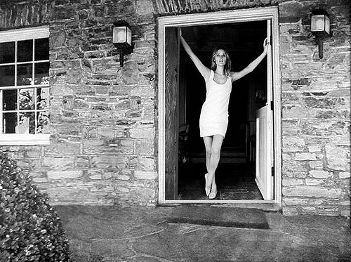 Sharon Tate standing in the infamous front door of 10050 Cielo Drive, early 1969