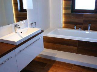Wyposażenie łazienki w bieli i drewnie w Leroymerlin. - Białe i błyszczące płytki w łazience które przywodzą na myśl nieskazitelną, wręcz sterylną czystość, elegancję, ale także chłód.