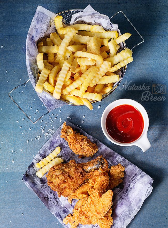 Fast Food - Chicken fries strips and legs on paper with basket of  French fries and bowl of ketchup sauce over blue wooden table. Top view
