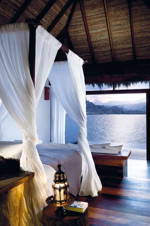 I love the canopy bed!! Such lovely sheers wrapped so elegantly around the bed posts. And just look at that view!