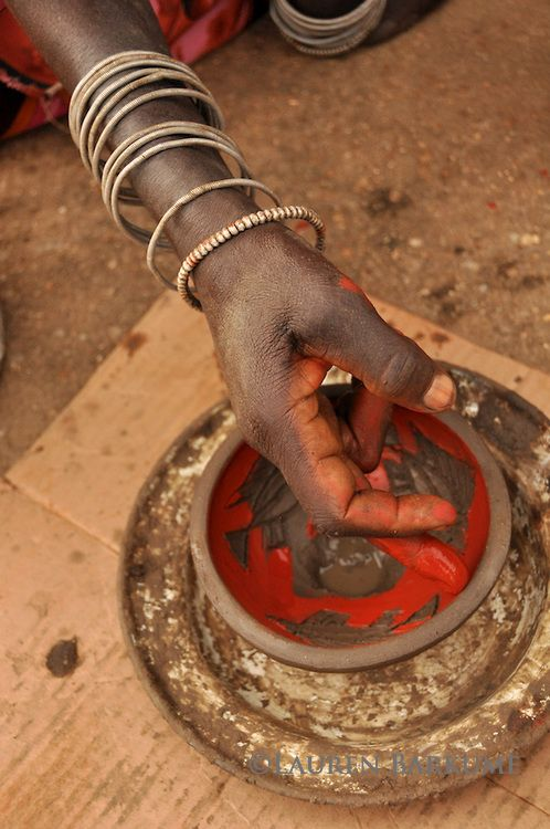 A woman from Mashamba Village Pottery carefully paints the wet clay with red…