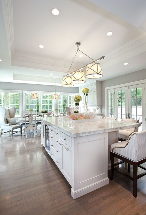 Gorgeous kitchen features tray ceiling accented with Grosvenor Linear Triple Pendant illuminating large center island fitted with glass-fron...