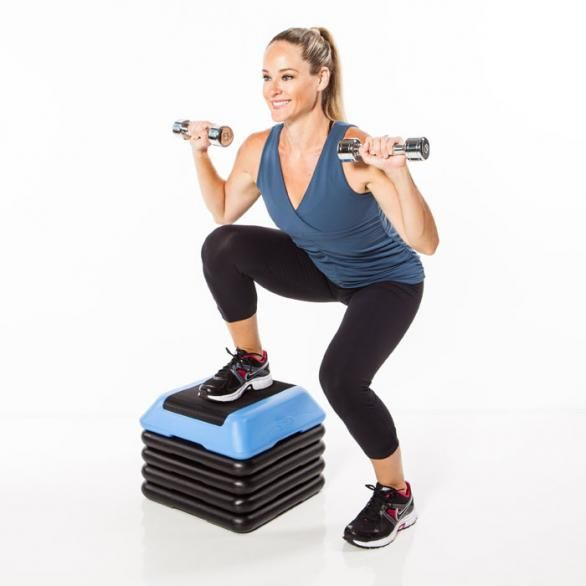 Grab a pair of dumbbells and stand to the right side of step. Place right foot flat on the center of the step and lower down into a squat, h...