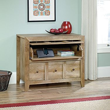 """This media cabinet is called the Anywhere Console for a reason! Use it in any room of the home as a TV stand with storage. Or you can display home décor on top and stow away household items in the drawers below. Either way, make a bold statement with this chest from the Dakota Pass collection. Finished in a traditional rustic country Craftsman Oak and detailed with a contemporary sensibility, this design looks great in any room. Holding up to a 42"""" TV, the nifty upper Vanishing Drawer™ with…"""