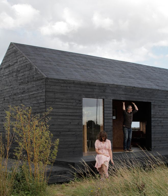 Carl Turner and Mary Martin pose on the porch of the Stealth Barn, a multipurpose structure that plays as a guest cottage, office space, ...