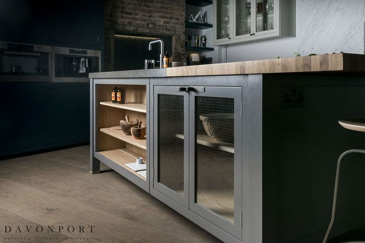 The island provides extra storage as well as a place to prepare food and a space for dining. The open-shelving set alongside a glazed cabinet with industrial glass provides a strong look that ties in perfectly with the rest of the room.
