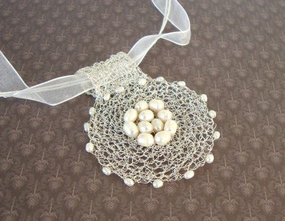 The pendant is created by crocheting silver plated wire and it is decorated with freshwater pearls.  Feminine, elegant, lightweight and eye-catching.