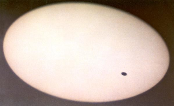 Jezus Geboorte - Een foto van Venus tussen aarde (waar de foto genomen werd) en de zon. Onderschrift van de foto: De planeet Venus (het zwarte schijfje dat op de foto tussen aarde en zon staat) mag op het eerste gezicht niets met Kerstmis te maken hebben, maar dat is onjuist. Planeten als Venus en Jupiter staan als heldere 'sterren' aan de hemel, maar zijn geen sterren. Ze zwerven (Grieks: planetos = zwervend) schijnbaar door sterrenbeelden heen en lijken soms erg dicht bij elkaar te staan…