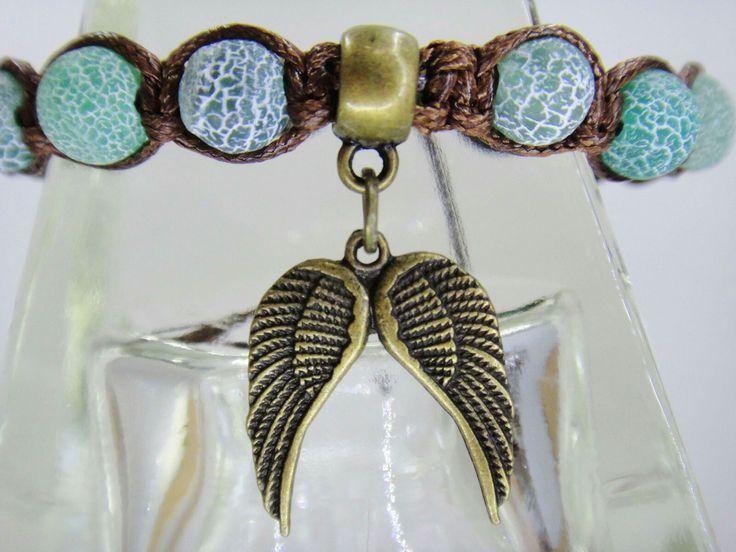 Pulsera de hilo marrón con cuentas naturales en verde. Dije alas de metal en oro viejo.