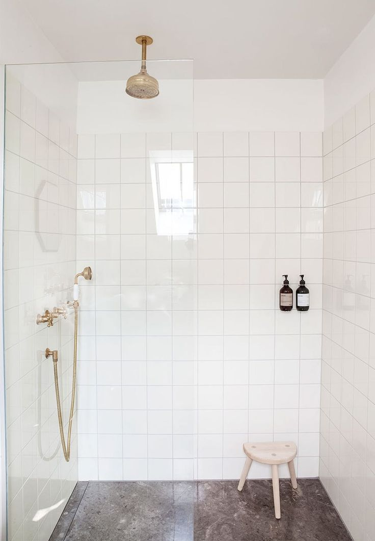 Simplicity in the bathroom - shower cabin with classic, cream white tiles and marble floors. The brass luminaire is from Toni.