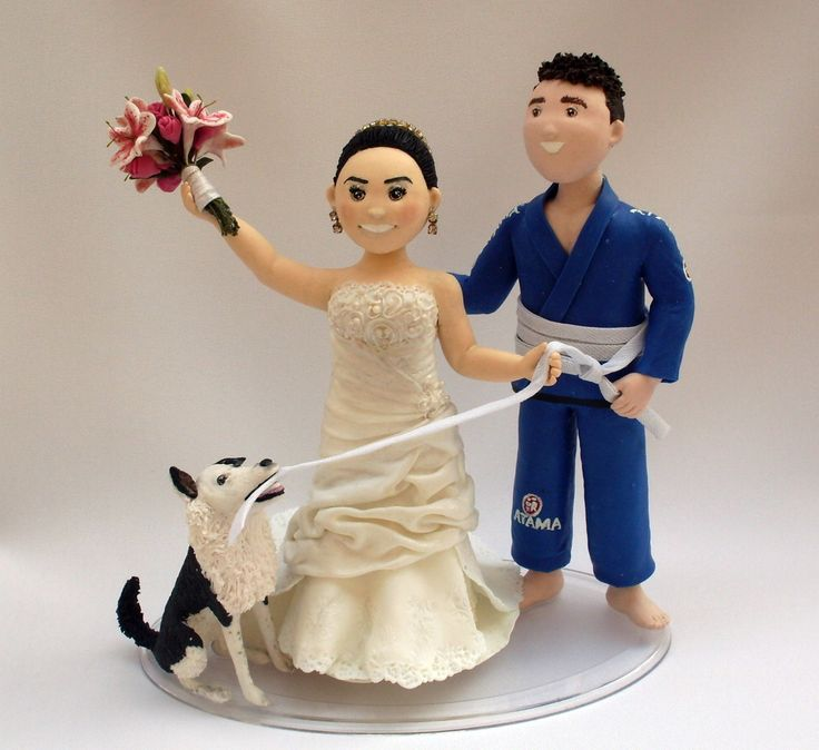 Noivinhos personalizados em BISCUIT. <br>Noiva com buquê levantado, puxando com o cachorro o Noivo lutador de jiu jitsu pela faixa do kimono.
