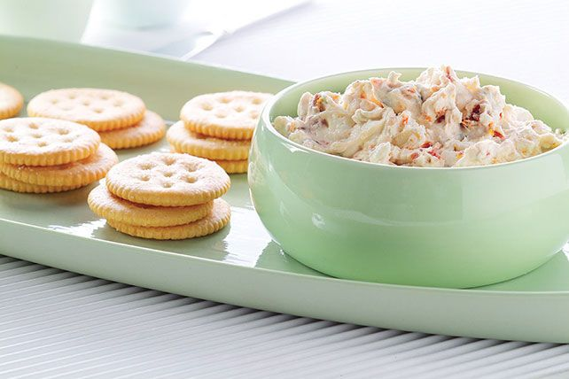 Cream cheese, feta, sun-dried tomatoes and fresh basil are blended into a Mediterranean-inspired appetizer spread to serve with crackers or veggies.