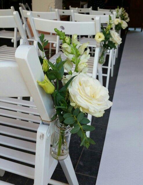 Bruiloft vaasjes witte bloemen aan stoelen