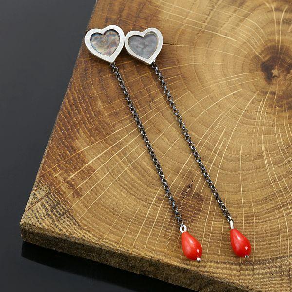 Urokliwe kolczyki sztyfty wykonane ze srebra próby 925. Drobne, wiszące kolczyki o minimalistycznej formie serc zakończone kroplami koralowca.