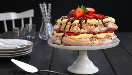 Den velkjente kaken Pavlova er en favoritt hos mange. Her har marengsen fått selskap av sjokolade, og mellom de sprø marengsbunnene lurer en fløyelsmyk eggekrem laget av trygge, norske egg og røde, friske jordbær. Smaken blir rett og slett himmelsk!