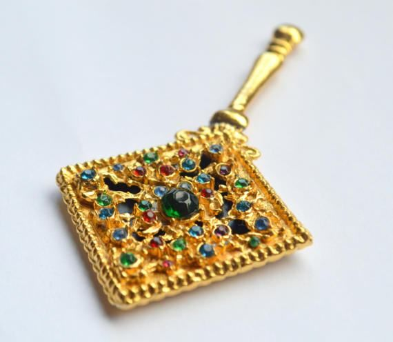 An adorable miniature mirror by the English Pygmalion from the 50s!  It is a gold tone with tiny filigree ornaments and a dozen or so small colour rhinestones and a bigger one in the centre. It comes with the original Pygmalion presentation box.  It measures 9 cm (3.5) long, and 4.5 cm (1.77) across and its in a very good vintage condition, the filigree side is in immaculate shape, a minor tarnish at the edges of the mirror.  Great find for the collectors or would make a charming gift to a…