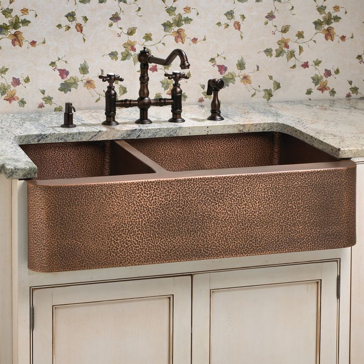Hammered copper farmhouse sink. Lovely fixtures too