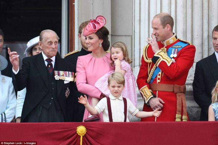 Are you not entertained? Prince George looks down at the crowd while Philip, medals on display, jokingly gestures