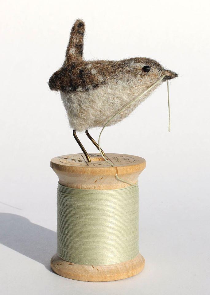 Bird on spool of thread