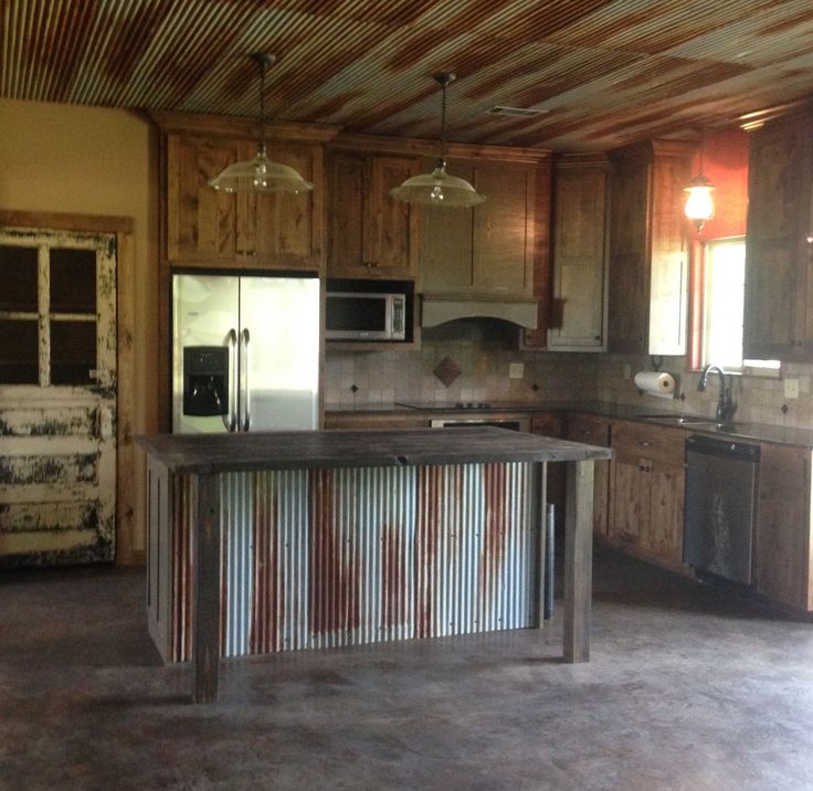 Rustic kitchen with old door for pantry door, custom made island, tin ceiling.