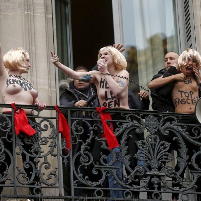 """Le forze dell'ordine francesi intervengono per interrompere una protesta del gruppo Femen a Parigi in occasione di un comizio di Marine Le Pen. Al grido di """"Heil Le Pen"""", in tre sono salite sul balcone di place de L'Opéra, dove la leader del Fronte Nazionale stava partecipando alle tradizionali celebrazioni di Giovanna D'Arco per il primo maggio"""