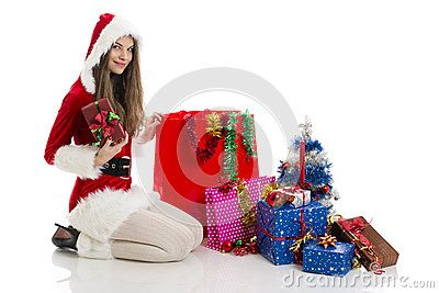 Beautiful Christmas sexy girl wearing Santa Claus clothes holding red gift box, near big shopping bags and presents, over white background.