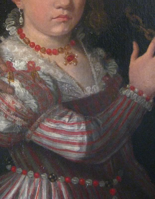 Necklace might be coral and gold beads, pendant likely gold with three pearls draped. Bracelet is pearl and coral. Girdle is coral and possibly pearls? They seem rather large and oddly transparent. 1560s Giovanni Antonio Fasolo, Paola Gualdo and Daughters Detail. This dress is worn by a teenager