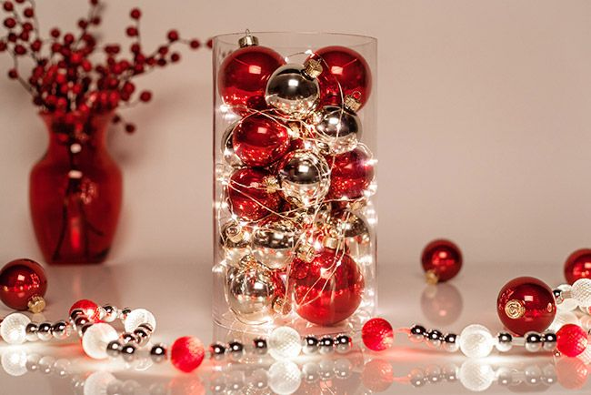 Create a glowing centerpiece for Christmas dinner using ornaments and fairy string lights!