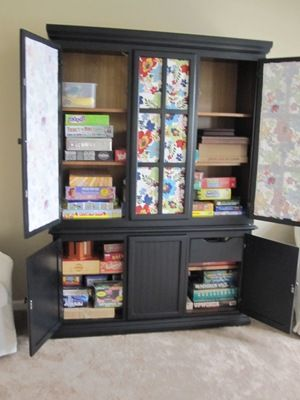 Great idea to store games in a hutch you no longer need (or find cheap at a yard sale). Paint a chalk wall on the inside of a door, and keep track of your family game night choice of the week!