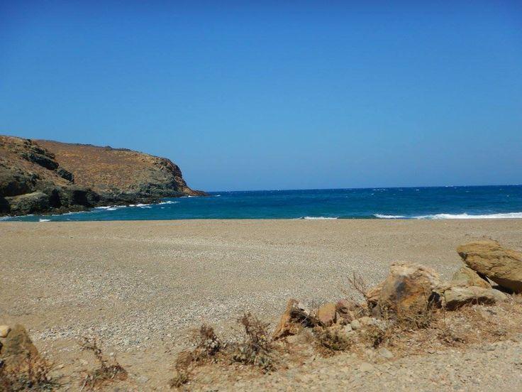 The remote Merchia beach a perfectly shaped semi circle facing out into the blue Aegean Sea.