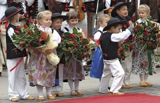 Children wear traditional clothing at a ceremony in Poland.