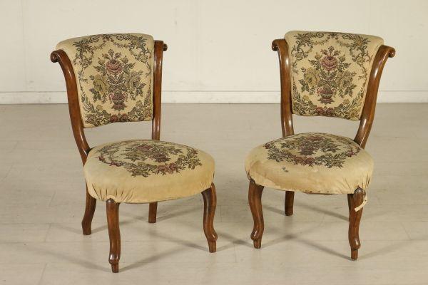 Coppia di sedie dalla linea mossa e intagliata. Seduta e schienale imbottiti.