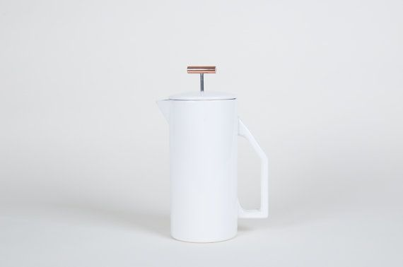 """*Backordered until end of January 2017*  850 mL Ceramic French Press. Brew perfect, full-bodied coffee in the traditional french press method. This heavy walled ceramic press pot is a functional and beautiful addition to your kitchen table. The ceramic body maintains a consistent temperature throughout the brewing process.  High gloss finish. Certified SGS Food Safe.   Materials: Fine Mesh Steel Filter Ceramic Pitcher & Lid Copper Pull  Dimensions: 7.5"""" Height, 3.5"""" Carafe Diameter, 5.5"""" ..."""