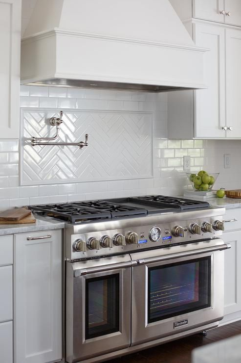 Chic kitchen features a white French kitchen hood which stands over a white herringbone cooktop backsplash lined with a swing arm pot filler and a Thermador stove with dual ovens.