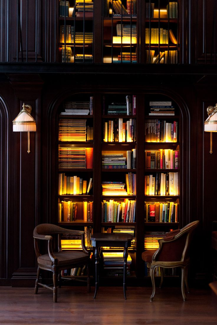 Black walls, lighted, arched bookcases and sconces - photo of the library at the Nomad Hotel by Alice Gao