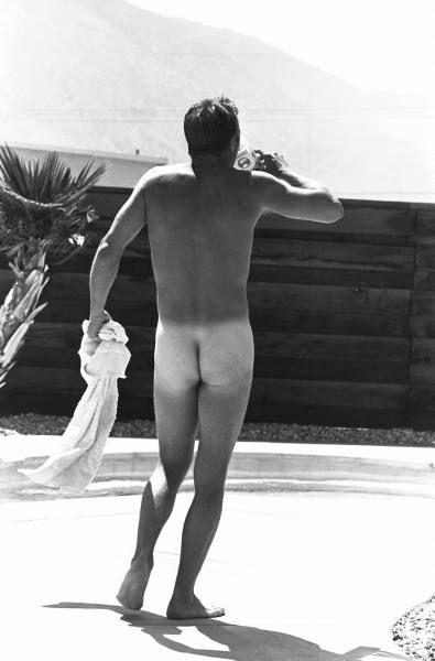 Actor Steve McQueen walking naked outdoors in his backyard. 1963