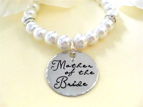 This pretty Mother of the Bride pearl bracelet is perfect for the Mother of the Bride! One lightly brushed aluminum disc with beveled edges is hand stamped with Mother of the Bride in cursive font and attached to a beautiful stretchie glass pearl bracelet with 3 stations of crystals. One size fits most. Mother of the Groom pearl bracelets are available, too. You can order one from my shop or select the quantity of 2 from this listing and let me know at checkout that youd also like a Mother…