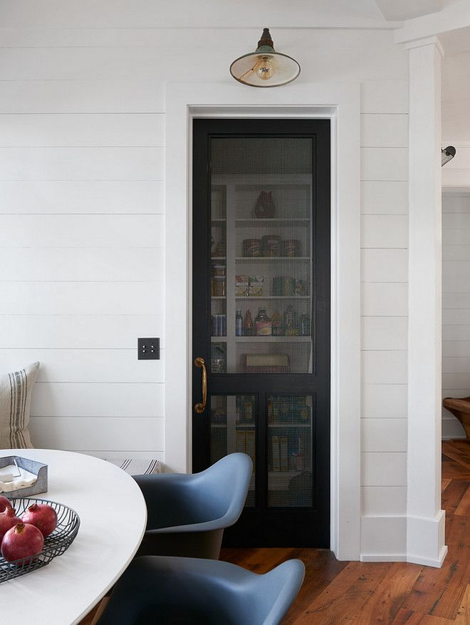 Farmhouse pantry with black mesh screen door, antique brass door handle, vintage barn sconce and shiplap paneled walls.