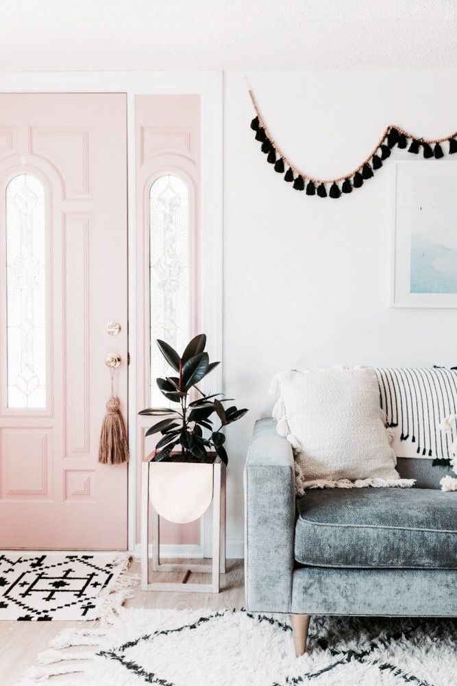 Feminine styled livingroom, love how the pink door matches with the blue velvet couch