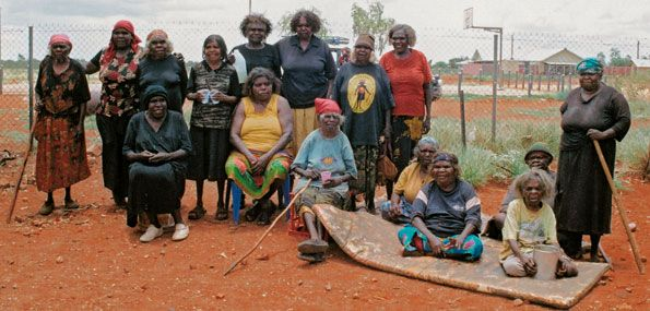 lopta-women, Papunya Tula Artists. Left to right, standing: Wintjya Napaltjarri, Eileen Napaltjarri, Kawayi Nampitjinpa, Tatali Napurrula, Josephine Napurrula, Yuyuya Nampitjinpa, Nanyuma Napangati, Narrabri Nakamarra, and far right, Kayi Kayi Nampitjinpa; seated, Pantjiya Nungurrayi, Irene Nangala, Nancy Nungurrayi, Naata Nungurrayi, Nyurapayia Nampitjinpa, in front, Ningura Napurrula and Makinti Napanangka, at Kintore, 2005. Photo: Paul Sweeney.